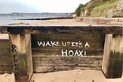 Covid 19 - Comment on the Coronavirus on a groyne on Swanage beach, Dorset UK June 2020