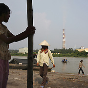 A young girl awaits customers at a riverboat landing outside the coal-powered electricty plant in Phai Lai, about 70 kilometers east of Hanoi, Vietnam, 14 September, 2007.