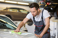 Young automobile mechanic cleaning car in repair shop