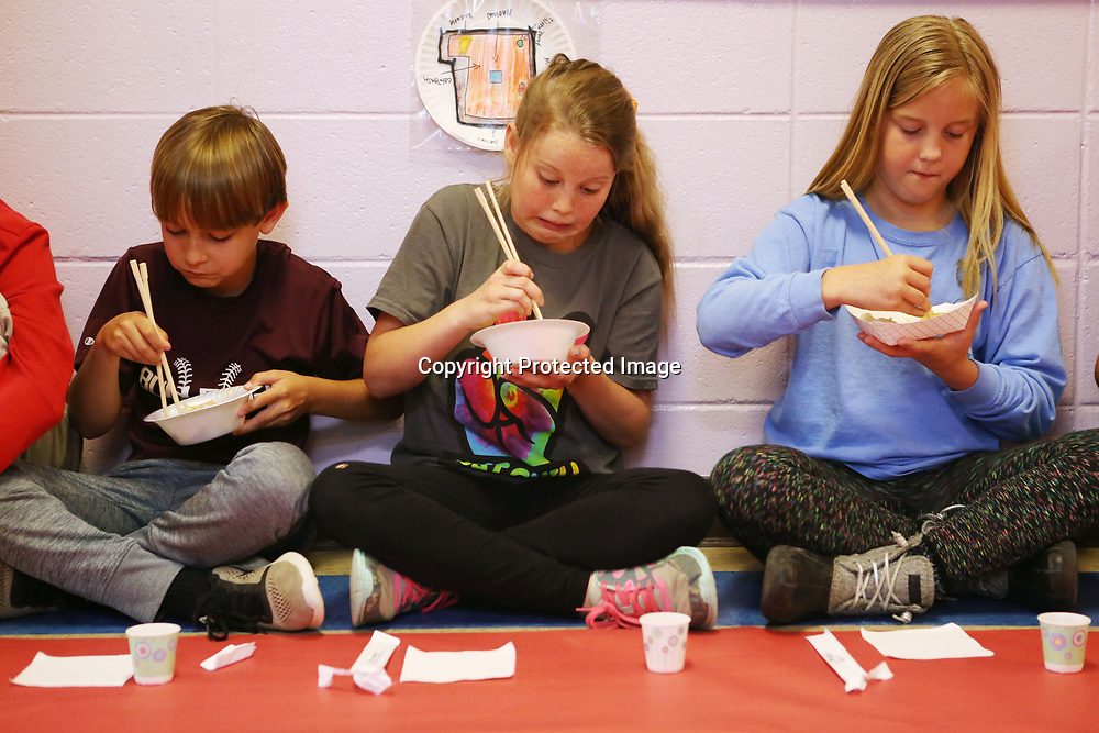 Saltillo Elementary School fourth graders Drake McNich, from left, Madison Russell and Emma Turner use chopsticks to eat hibachi chicken and rice during their Japanese culture day at the culmination of their unit on the country and it's culture. Six fourth grade classrooms totaling to 138 students studied the Asian culture.