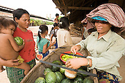 30 JUNE 2006 - PHNOM PENH, CAMBODIA: A fruit vendor sells watermelon to the wives and children of brick factory workers at a brick factory in Phnom Penh, Cambodia. This particular factory employs about 30 people. The live on the premises with their families. Most of the workers migrated to Phnom Penh from the countryside looking for better paying jobs than they could find in the countryside. According the United Nations Food and Agricultural Organization, there are more than 70 brick factories in Phnom Penh and its environs. Environmentalists are concerned that the factories, most of which burn wood in their kilns, contribute to deforestation in Cambodia. They are encouraging factory owners to switch to burning rice husks, as brick kilns in neighboring Vietnam do. The brick factories are kept busy feeding Phnom Penh's nearly insatiable appetite for building materials as the city is in the midst of a building boom brought by on economic development and the need for new office complexes and tourist hotels.   Photo by Jack Kurtz / ZUMA Press