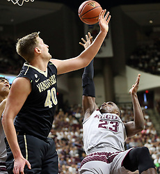 Texas A&M's Danuel House (23) is fouled by Vanderbilt's Josh Henderson (40) while making a shot during the first half of an NCAA college basketball game, Saturday, March 5, 2016, in College Station, Texas. (AP Photo/Sam Craft)