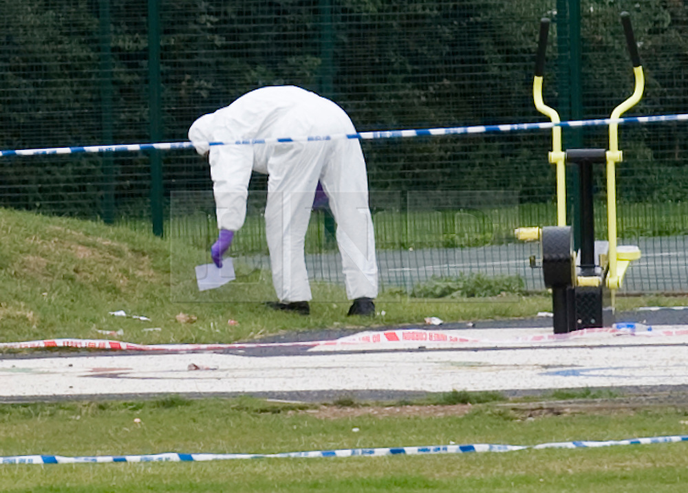 © Licensed to London News Pictures. 18/08/2011. A Police forensics officer examines an item on the floor in Ponders End Recreation Ground in Enfield, London today (18/08/2011) where 14 Year-old Leroy James was found stabbed to death yesterday afternoon. Photo credit: Ben Cawthra/LNP