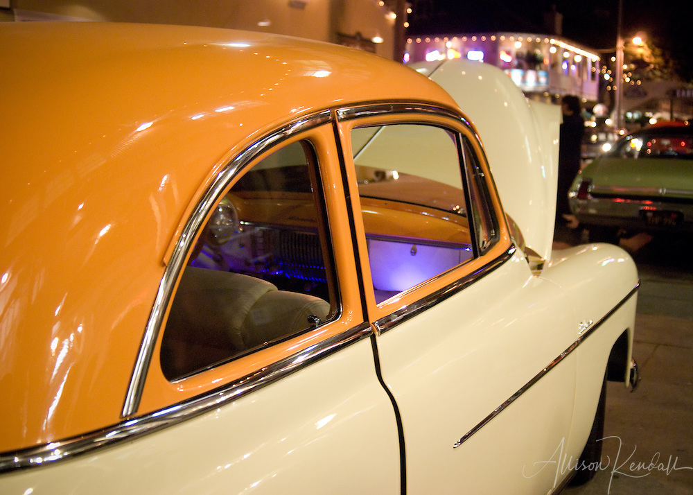 Glowing purple and orange, a vintage hotrod classic car sits on display surrounded by the lights of Cannery Row in Monterey
