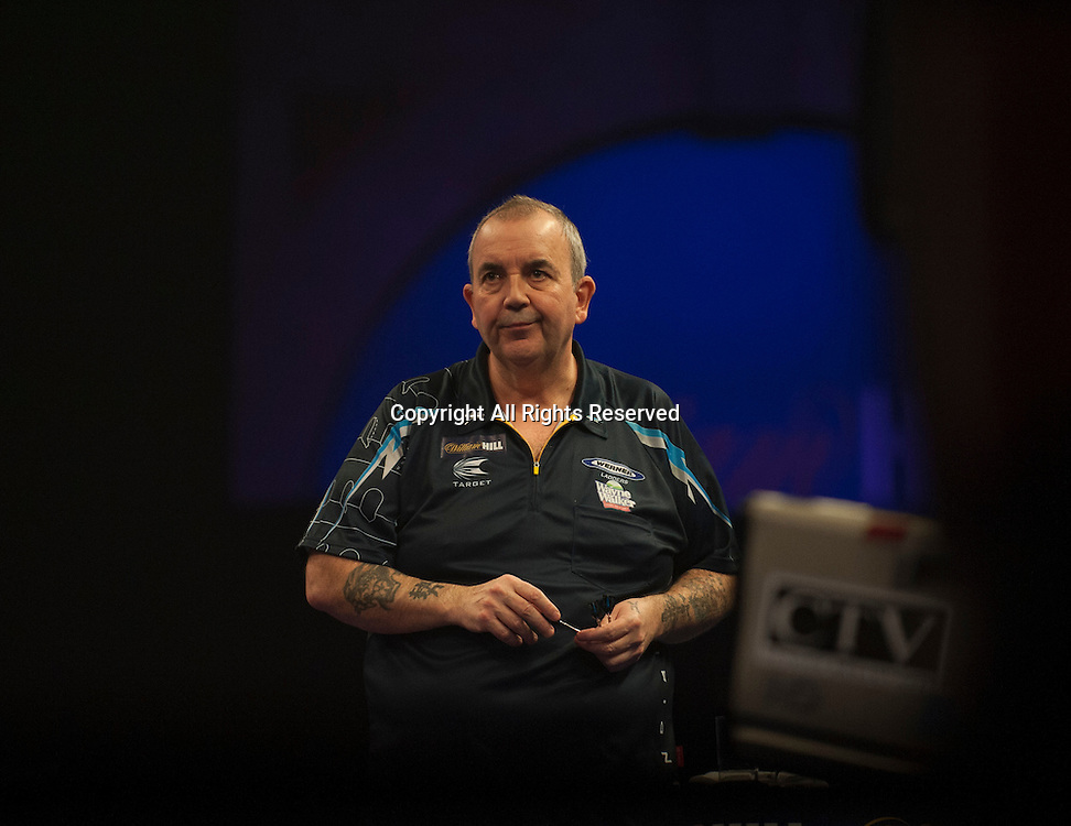02.01.2014.  London, England.  William Hill PDC World Darts Championship.  Quarter Final Round.  Phil Taylor (2) [ENG] looks concerned during his game with Vincent van der Voort (23) [NED]. Phil Taylor won the match 5-3