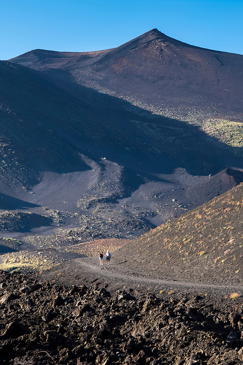 Tourists walking on Lava field caused by volcanic eruption of Mount Etna active stratovolcano at Taormina, Sicily, Italy