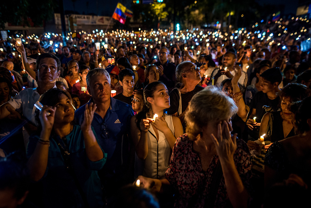 """CARACAS, VENEZUELA - MAY 17, 2017: People light candles during a vigil in memory of members of """"The Resistance"""" killed by authorities during street protests. The streets of Caracas and other cities across Venezuela have been filled with tens of thousands of demonstrators for nearly 100 days of massive protests, held since April 1st. Protesters are enraged at the government for becoming an increasingly repressive, authoritarian regime that has delayed elections, used armed government loyalist to threaten dissidents, called for the Constitution to be re-written to favor them, jailed and tortured protesters and members of the political opposition, and whose corruption and failed economic policy has caused the current economic crisis that has led to widespread food and medicine shortages across the country.  Independent local media report nearly 100 people have been killed during protests and protest-related riots and looting.  The government currently only officially reports 75 deaths.  Over 2,000 people have been injured, and over 3,000 protesters have been detained by authorities.  PHOTO: Meridith Kohut"""