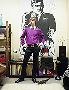 Young man dressed in Mod style clothing standing in front of vinyl records and record player.