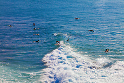 Unidentified surfers catching a wave off the northwest coast of Maui.