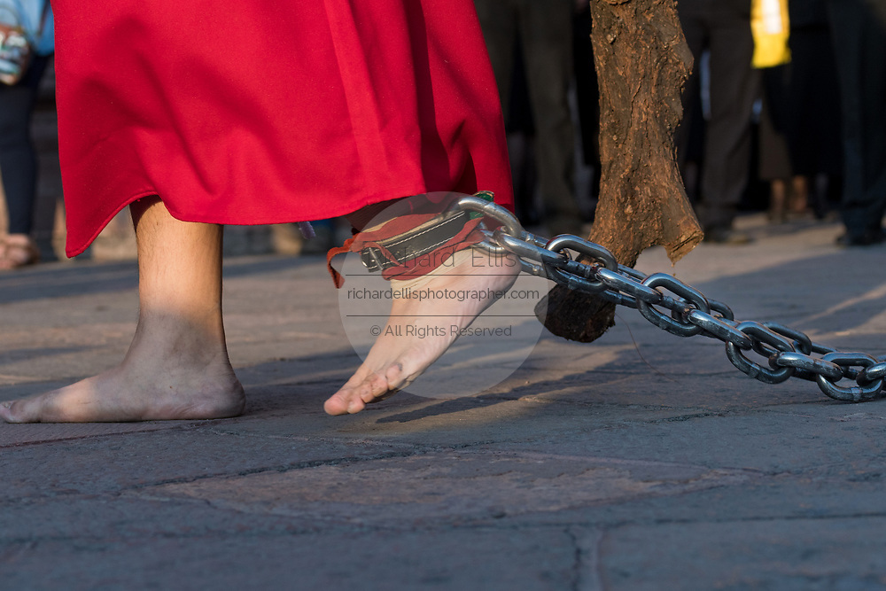 A hooded penitent carries a heavy wooden cross and drags a steel chain through the city streets during the Procession of Silence as part of Holy Week March 30, 2018 in Querétaro, Mexico. The penitents, known as Nazarenes, carry heavy crosses and drag chains in a four hour march to recreate the pain and suffering during the passion of Christ.