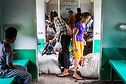 15 JUNE 2013 - YANGON, MYANMAR:  Women step into the door of the Yangon Circular Train before the train pulls into their station. The Yangon Circular Railway is the local commuter rail network that serves the Yangon metropolitan area. Operated by Myanmar Railways, the 45.9-kilometre (28.5mi) 39-station loop system connects satellite towns and suburban areas to the city. The railway has about 200 coaches, runs 20 times and sells 100,000 to 150,000 tickets daily. The loop, which takes about three hours to complete, is a popular for tourists to see a cross section of life in Yangon. The trains from 3:45 am to 10:15 pm daily. The cost of a ticket for a distance of 15 miles is ten kyats (~nine US cents), and that for over 15 miles is twenty kyats (~18 US cents). Foreigners pay 1 USD (Kyat not accepted), regardless of the length of the journey.     PHOTO BY JACK KURTZ