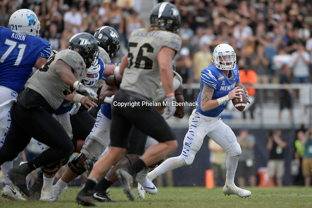 Memphis quarterback Riley Ferguson (4), right, rolls out to throw a pass against Central Florida during the second half of the American Athletic Conference championship NCAA college football game Saturday, Dec. 2, 2017, in Orlando, Fla. Central Florida won 62-55. (Photo by Phelan M. Ebenhack)