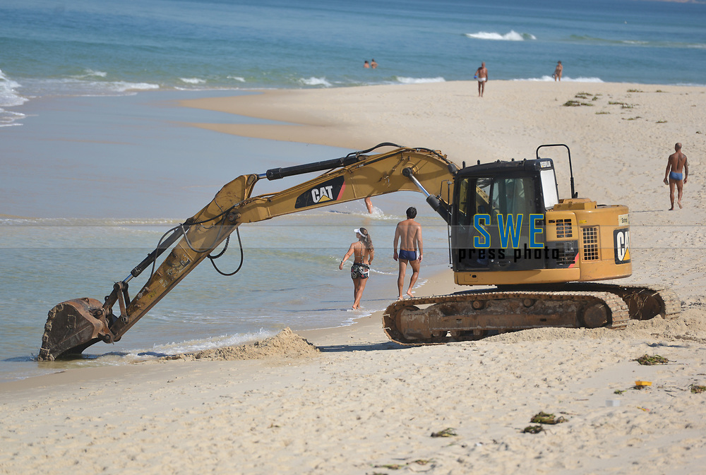 Rio de Janeiro-Brazil12 May 2020 population forbidden to go to the beach, disobey the amount and take a risk walking in the middle of the construction of Barra da Tijuca beach, one of the main beaches in the city of Rio de Janeiro