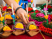 "17 NOVEMBER 2013 - BANGKOK, THAILAND:  A Krathong vendor puts incense and candles into krathongs he is selling near Wat Yannawa in Bangkok. Loy Krathong (also written as Loi Krathong) is celebrated annually throughout Thailand and certain parts of Laos and Burma (in Shan State). The name could be translated ""Floating Crown"" or ""Floating Decoration"" and comes from the tradition of making buoyant decorations which are then floated on a river. Loi Krathong takes place on the evening of the full moon of the 12th month in the traditional and they do this all evening on the 12th month Thai lunar calendar. In the western calendar this usually falls in November. The candle venerates the Buddha with light, while the krathong's floating symbolizes letting go of all one's hatred, anger, and defilements      PHOTO BY JACK KURTZ"