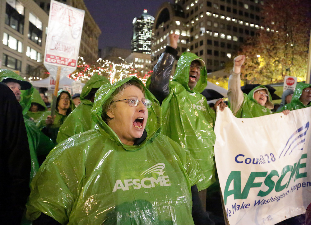 Julianne Moore (L) of the American Federation of State County and Municipal Employees (AFSCME) chants during a rally organized by the Washington State Labor Council to show support for the Boeing Machinists union at Westlake Park in Seattle, Washington November 18, 2013. The International Association of Machinists and Aerospace Workers union rejected a contract offer Wednesday that Boeing said was necessary for the new 777 jetliner to be built in Washington.