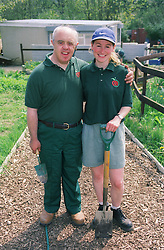 Man with Downs Syndrome and carer in garden,
