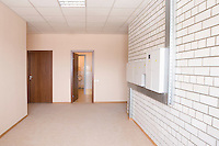 Tiled wall with fusebox in wide hallway