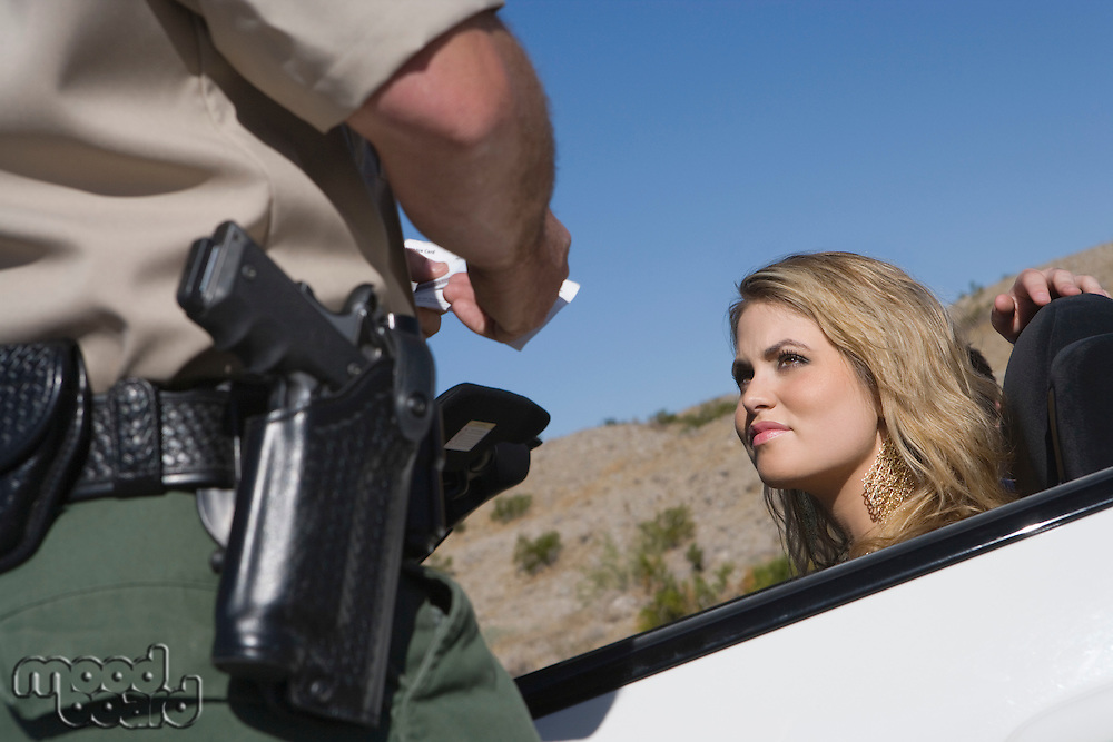 Policeman writing young woman speeding ticket