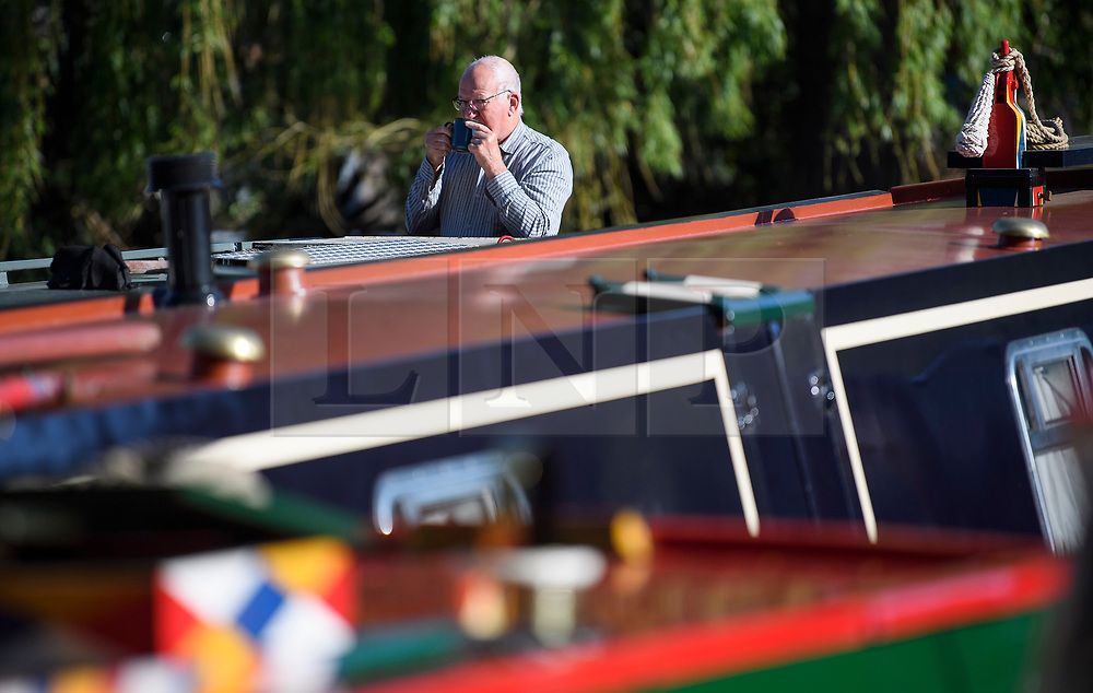 © Licensed to London News Pictures. 04/05/2019. London, UK. A boat owner drinks a cup of tea in the early morning sunshine during the Canalway Cavalcade festival in Little Venice, West London on Saturday, May 4th 2019. Inland Waterways Association's annual gathering of canal boats brings around 130 decorated boats together in Little Venice's canals on May bank holiday weekend. Photo credit: Ben Cawthra/LNP