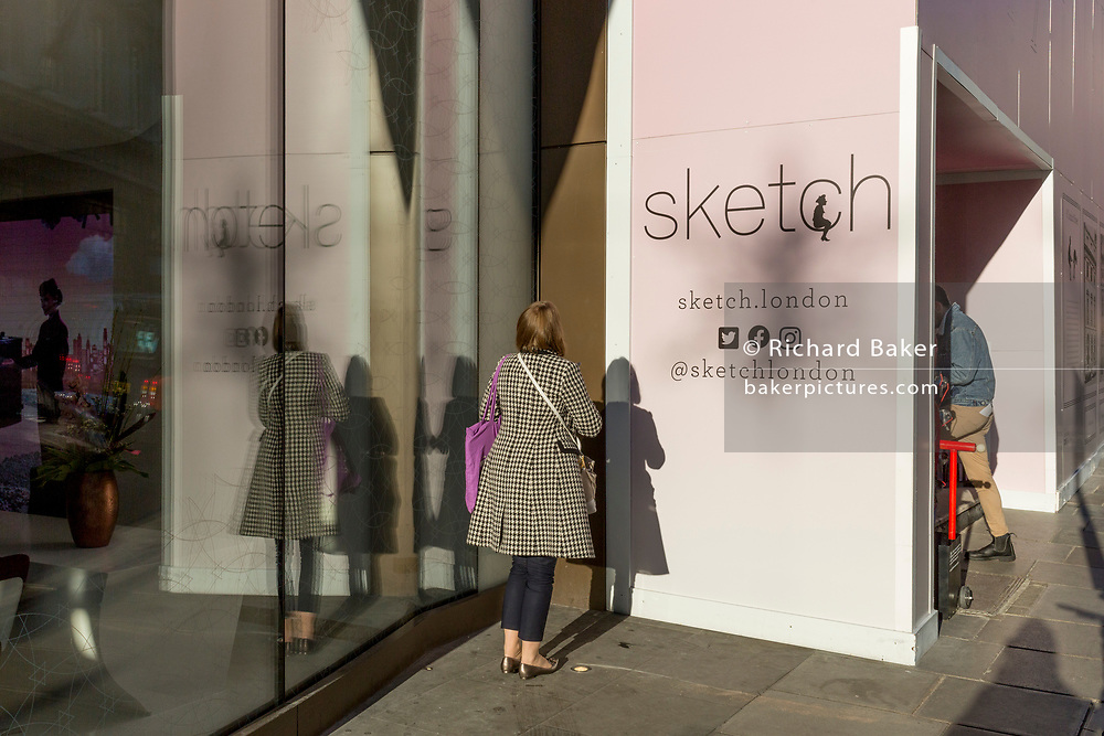 A young woman holds a private phone conversation in a sunny corner next to 'Sketch', a gastro-gallery on Conduit Street, on 20th January 2020, in London, England.