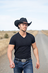 sexy cowboy walking on a rural dirt road
