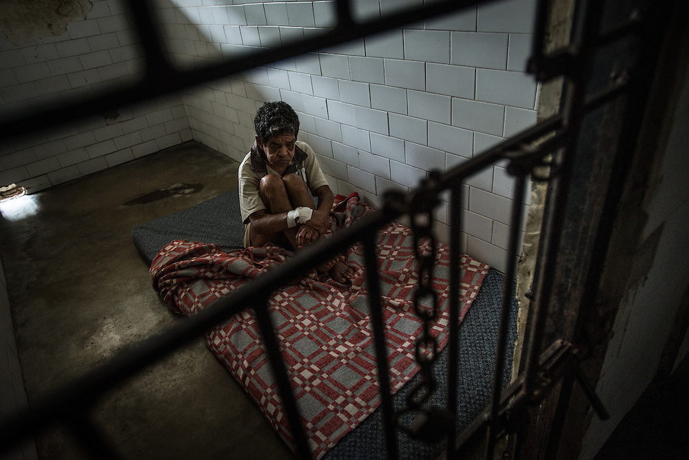 BARQUISIMETO, VENEZUELA - JULY 28, 2016:  Josefina Zapata, a patient diagnosed with psychosis and epilepsy, sits in solitary confinement. She does not have 5 of the 6 medicines prescribed to her, and regularly suffers from epileptic seizures that would be avoided if she had all the medicines that she needs. She is not violent, but the hospital staff regularly keep her locked in a very small isolation cell, on a mattress on the floor so that if she starts convulsing, she is less likely to hurt herself. The economic crisis that has left Venezuela with little hard currency has also severely affected its public health system, crippling hospitals like El Pampero Psychiatric Hospital by leaving it without the resources it needs to take care of patients living there, the majority of whom have been abandoned by their families and rely completely on the state to meet their basic needs. The hospital has not employed a psychiatrist for over two years. Drugs used to combat bipolar disorder, epilepsy, schizoaffective disorder and chronic anxiety are now in short supply, as are numerous sedatives and tranquilizers needed to care for patients. PHOTO: Meridith Kohut for The New York Times