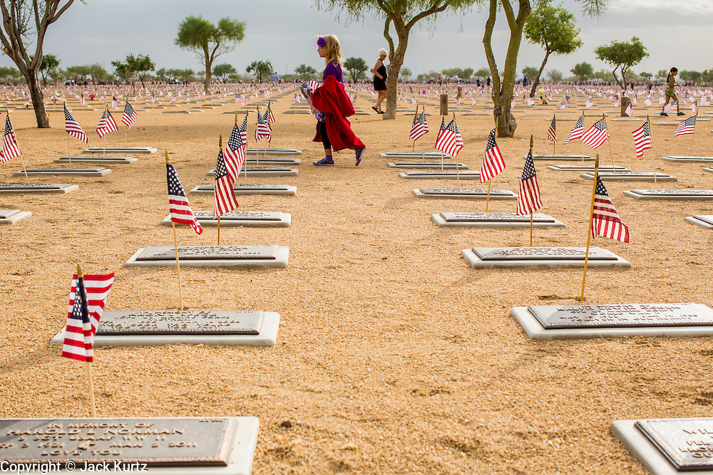 26 MAY 2012 - PHOENIX, AZ:  A girl walks through the National Memorial Cemetery in Phoenix, AZ, Saturday. Hundreds of Boy and Girl Scouts along with the Young Marines, a Scout like organization, place American flags on veterans' graves in the National Memorial Cemetery in Phoenix every year on the Saturday before Memorial Day.       PHOTO BY JACK KURTZ