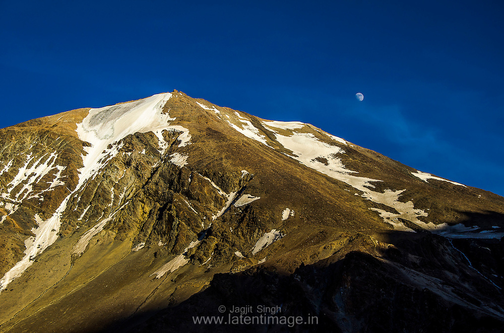 Snow peaked mountain on the way to Leh, Moon view in clear sky.