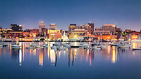 The city of Portland Maine rises above the waters of Portland Harbor, which is filled with sailing vessels and pleasure boats. The landmark Time and Temperature building can be seen, reading 5:39.