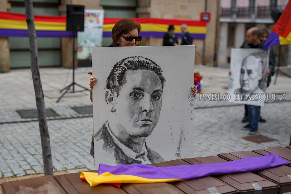 14/04/2018. A portrait depicting Spain's Civil war victim Elicio Gomez is hold by a relative next to coffins containing the bodies of victims of Spain Civil War exhumed in Cobertelada and Calata&ntilde;azor placed on a bench in the center of Soria during a homage to hand the remains to their relatives on April 14, 2018 in Soria, Spain. La Asociacion Soriana Recuerdo y Dignidad (ASRD) 'The Soria Association for Memory and Dignity' celebrated a tribute to hand over the remains of civil war victims to their families. The Society of Sciences of ARANZADI helped with the research, exhumation and identification of the bodies, after villagers passed the information about the mass grave, 81 years after the assassination took place, to the ASRD. Seven people were assassinated around August 25, 1936 by Falangists, as part of General Francisco Franco armed forces, and buried in the 'Fosa de los Maestros' (Teachers Mass Grave) near Cobertelada, Soria, after being taken from prison of Almazan during the Spanish Civil War. Five of them were teachers in the region, and also friends of Spanish writer Antonio Machado. The other two still remain unidentified. Another body was assassinated by Falangists accompanied by a priest in 1936, and was exhumed on 23 September of 2017 near Calata&ntilde;azor, Soria. It belonged to Abundio Andaluz, a politician, lawyer and musician in Soria.<br /> Spain's Civil War took the lives of thousands of people on both sides, and civilians. But Franco continued his executions after the war has finished. Teachers, as part of the education sector, were often a target of Franco's forces. Spanish governments has never done anything to help the victims of the Civil War and Franco's dictatorship while there are still thousands of people missing in mass graves around the country. (&copy; Pablo Blazquez)