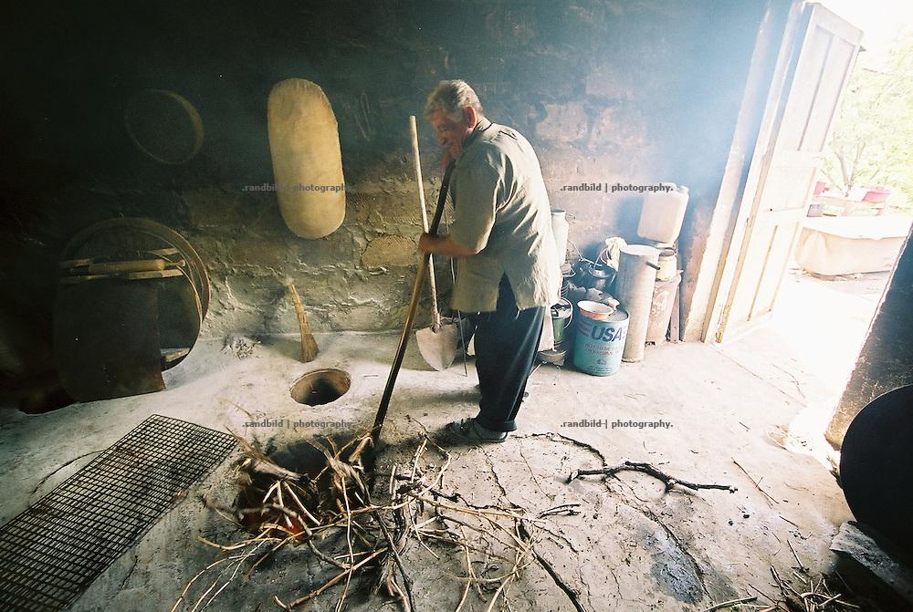 Ein pensionierter Ingenieur wirft Holz in den Tonir, den traditionellen armensichen Erdofen. Vor allem auf dem Land wird noch in den Öfen Brot gebacken und bei Festlichkeiten Fleischgerichte zubereitet. An elder armenian grills some chicken meat in the traditional Tonir stove which is built into the ground.