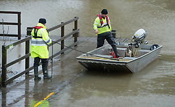 © London News Pictures. 30/12/2013. Yalding, UK.  Members of the Environment Agency use a boat to inspect the banks of the river Medway at Yalding in Kent, an area previously hit by flooding. The UK is braced for more bad weather after heavy rainfall caused flooding in parts last week.  . Photo credit : Ben Cawthra/LNP