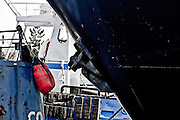 An iron anchor sits snugly against the deep blue hull of a ship in Seattle