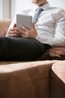 Midsection of businessman holding digital tablet on sofa at home