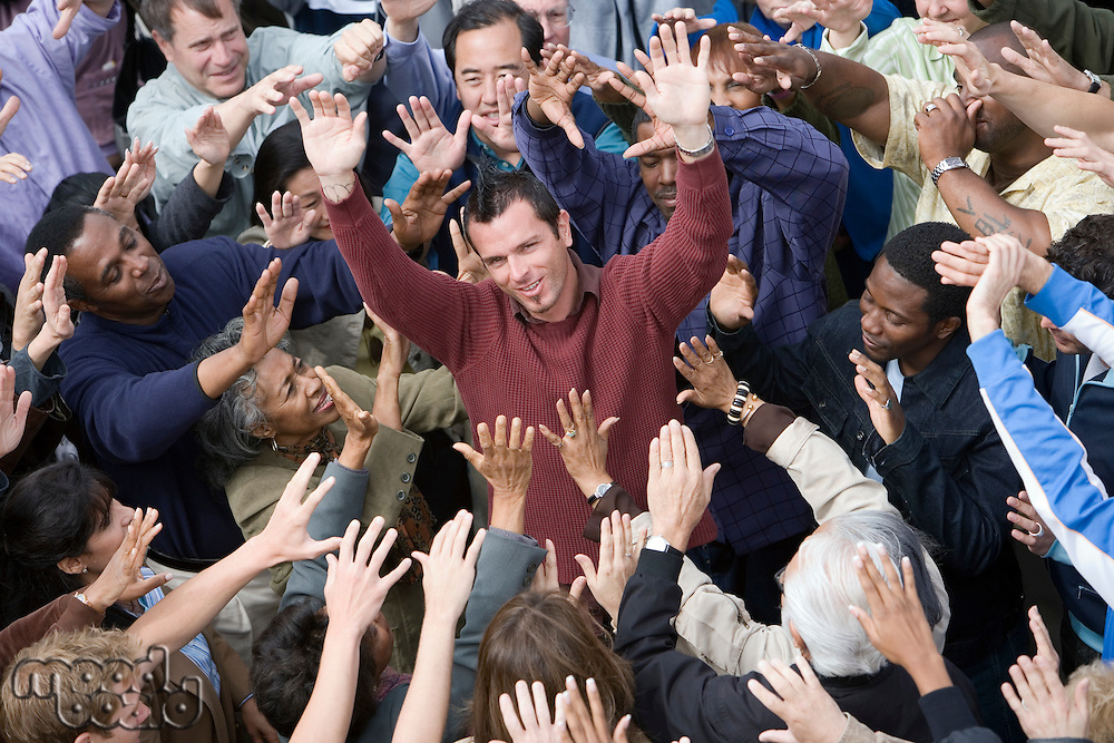 Crowd with arms raised surrounding man