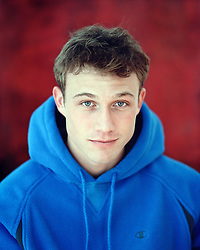 young man in a hooded sweatshirt looking at camera