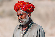 Portrait of an ethnic Rajasthani man who belongs to teh Rabari tribe wearing bright red turban known as the saafa