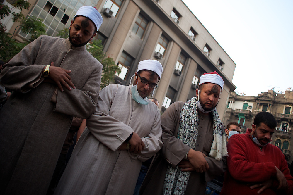 Egyptian men pray during violent clashes between security forces and protestors in central Cairo.