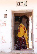 Woman villager hiding face with veil in doorway of home in Nalu, Rajasthan, India. The Swastika is a ancient symbol of good luck in India.