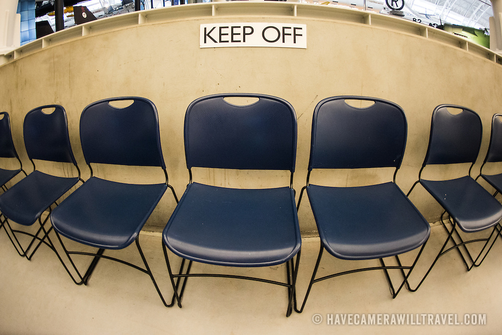 A sign warns people to keep off in front of a row of chairs. Located near Dulles Airport, the Udvar-Hazy Center is the second public facility of the Smithsonian's National Air and Space Museum. Housed in a large hangar are a multitude of planes, helicopter, rockets, and space vehicles.