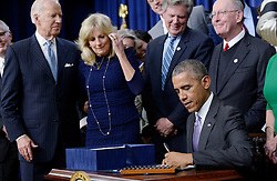 """President Barack Obama signs the 21st Century Cures Act, as Vice President Joe Biden (L) and Dr Jill Biden (2-L)look on in Washington, DC, December 13, 2016. The bill speeds up the approval process for new drugs and medical devices and expands funding for medical research, including the """"cancer moonshot"""" initiative led by Vice President Joe Biden. Photo by Olivier Douliery/ABACA"""