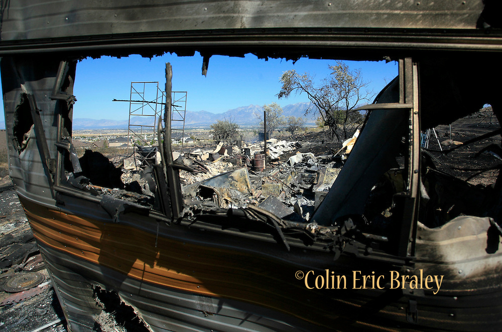 A destroyed structure is seen through the window of a burned out camping trailer Monday, Sept. 20, 2010, in Herriman, Utah. The blaze which forced the evacuation of more than 1,600 homes, was started by live-fire exercises at Camp Williams, a Army National Guard base southwest of Salt Lake City.. (AP Photo/Colin E. Braley)