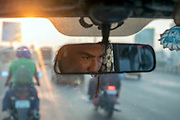 A taxi driver reflected in a rearview mirror of a taxi in Mumbai, India,