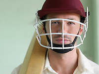 Cricket player wearing helmet and holding bat close-up portrait