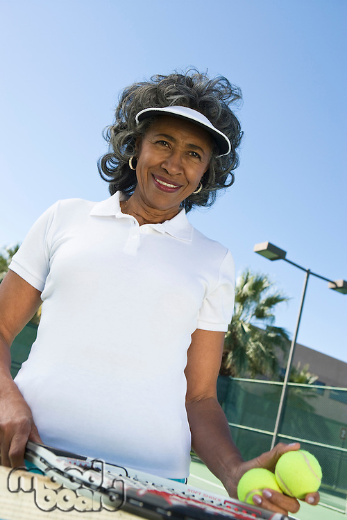 Woman holding tennis racket, portrait