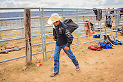 14 JULY 2012 - OAK SPRINGS, AZ:  A bull riding student walks out of the Aspen Canyon Rodeo Club with his gear after a bull riding class. The bull riding class was offered by the Crooked Horn Cattle Co. in the community of Oak Springs on the Navajo Nation, about 15 miles south of Window Rock, AZ. Eleven cowboys signed up for bull riding classes and one signed up for bull fighting classes. The bull riding class started with lessons on a mechanical bucking machine before the cowboys rode bulls.    PHOTO BY JACK KURTZ
