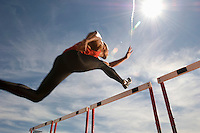 Runner jumping over running hurdle low angle view