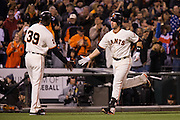 San Francisco Giants catcher Buster Posey (28) high fives San Francisco Giants third base coach Roberto Kelly (39) after hitting a home run against the Colorado Rockies at AT&T Park in San Francisco, Calif., on September 27, 2016. (Stan Olszewski/Special to S.F. Examiner)