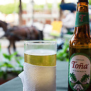 A glass of Toña Cerveza at a table overlooking Parque Central, with a horse-drawn carriage passing in the background. Parque Central is the main square and the historic heart of Granada, Nicaragua.