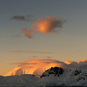 A small puff of cloud and a mountain catch the rays of the setting sun at Paradise Harbor, Antarctica.